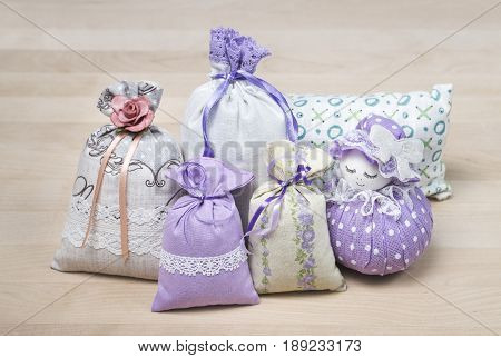Bunch of different scented sachets for decoration on wooden board. Many fragrant pouches on table. Aromatic potpourri set. Bags filled with lavender. Decorative interior design items on table.
