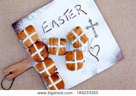 Easter - Hot Cross Buns hot cross buns on floured wooden cutting board, with word Easter written in flour - with silver cross