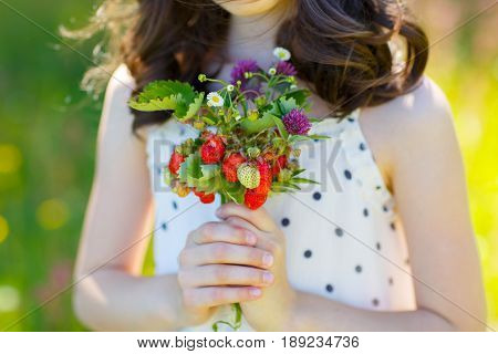 Girl in a dress with a pea in her hands holding a bouquet of flowers and wild berries