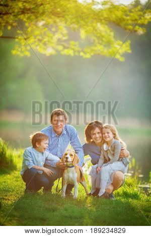 A large family is walking his beagle in a park by the lake. Mom Dad son and daughter are sitting on the grass under a tree on a warm summer evening