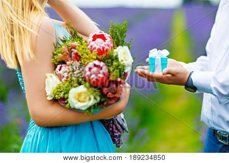 The man's hands stretch out a small gift box with a bow offering her to marry. She stands in a turquoise dress in the middle of a lavender field holding a lush bouquet of flowers in her hands