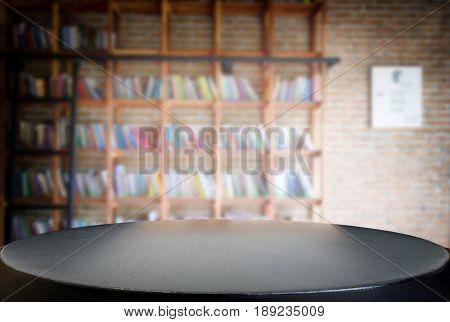 Selected focus empty black wooden table and Library or Bookstore blur background with bokeh image. for your photomontage or product display.