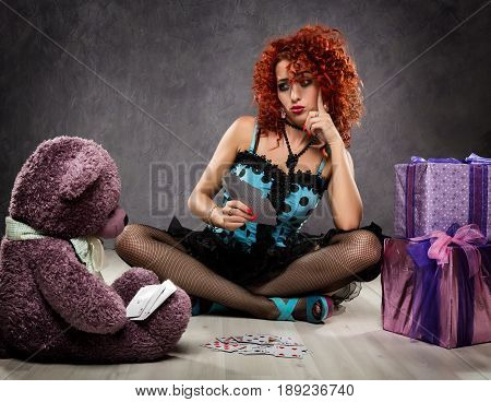 popsy play cards with a teddy bear. Curly redhead sexy girl looks like a doll for adult men. Beside gift boxes