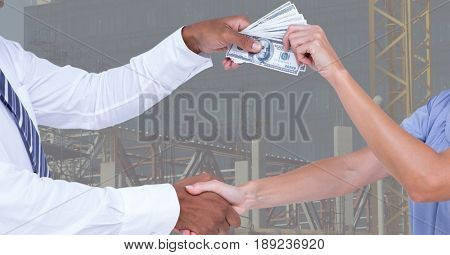 Digital composite of Business people shaking hands while passing money representing corruption concept
