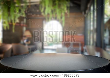 Selected focus empty black wooden table and coffee shop cafe or restaurant blur background image. for your photomontage or product display.