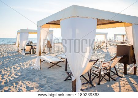 Wooden sunbeds in front of a turquoise sea with a blue sky