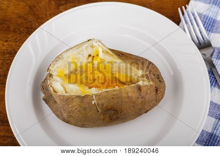 A hot baked potato on a white plate and wood table