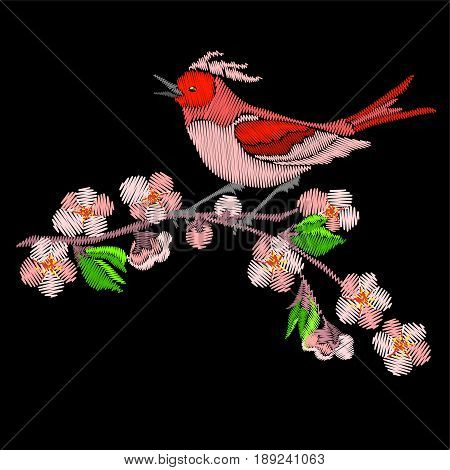 Embroidery bird and sakura blossom flowers on branch of tree isolated on black background.