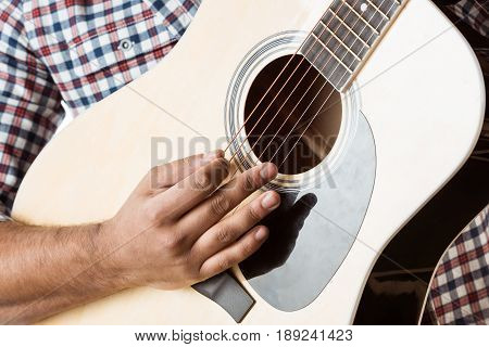 Close up partial view of man in shirt playing acoustic guitar