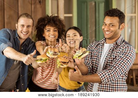 Young Smiling Multiethnic Friends Holding Burgers At Picnic On Patio