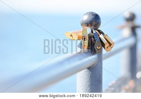 Metal padlocks hanging on the fence, on the background of blue sea. Closeup