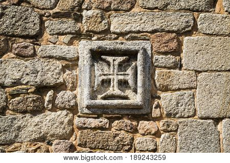 The insignia of the Order of Christ (Cross of the Order of Christ) in as old stone wall in the historic village of Idanha a Velha in Portugal