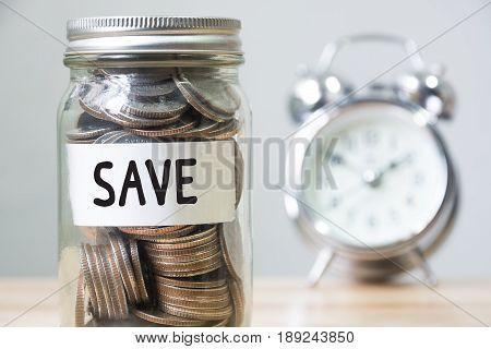 Money coin in jar with clock and text save Concept save money and time management