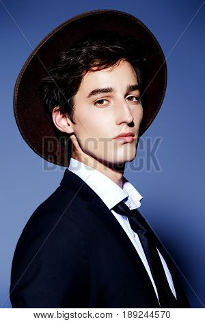 Fashion shot. Portrait of a handsome young man posing in elegant black suit, white shirt and a hat. Studio shot.