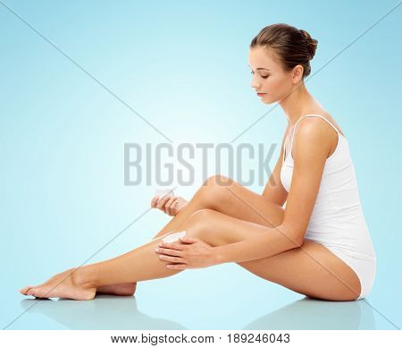 people, bodycare and beauty concept - beautiful woman applying moisturizing cream to her leg over blue background
