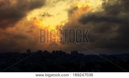 Sunset with huge cumuli clouds over the city. Jerusalem sunset at night dusk.