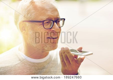 technology, senior people, lifestyle and communication concept - close up of happy old man using voice command recorder or calling on smartphone outdoors