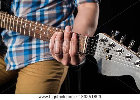 Music and art. Electric guitar in the hands of a guitarist on a black isolated background. Playing guitar