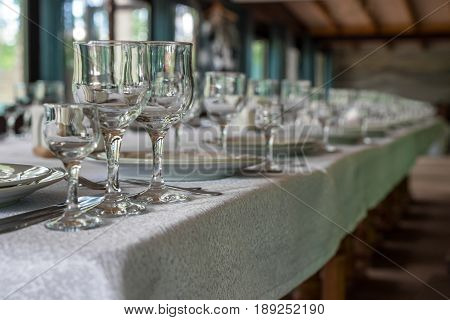 Interior Of The Restaurant, Cafe. Tables With Dishes, Plates, Woks, Knives, Glasses And Glasses, Pre