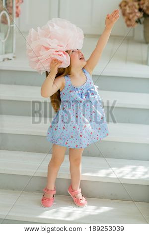 A little girl in a blue dress tries on her head a huge pink bow. She pulls her hand up looking with hope in the heavens