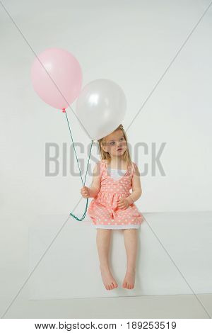 A small girl in a pink dress with polka dots sits on a clean white box holding two balloons in her hands. She is surprised and thoughtful