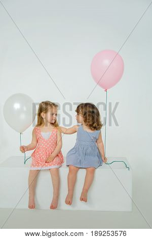 Two girlfriends are sitting on a white box holding balloons in their hands. Girl stroking girlfriend's hair curiously studying hairstyle