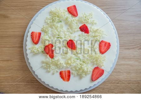 Delicious cheese cake decorated with fresh strawberries and elderflower