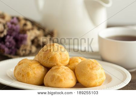 Homemade cream puffs or eclaire filled with vanilla custard cream. Golden choux cream on white plate put on rustic wood table. Cream puffs serve with tea in white pot or cup of coffee. Cream puffs or choux cream or eclairs. French pastry : cream puffs.
