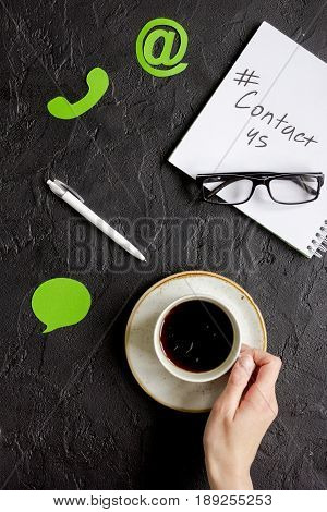 Customer Support Service Desktop With Contact Us Signs And Coffee On Dark Background Top View