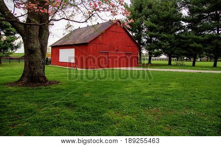 Red Kentucky Barn. Rural red barn with picket fence in the background. This structure is located in a Kentucky State Park and not private property.