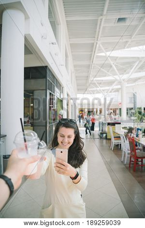Woman Drinking Smoothie while walking the mall man firt-person view