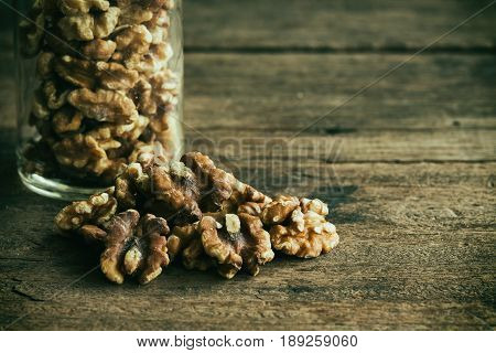 Baked walnuts for snack and bakery. Walnuts is good for health diet food raw material or ingredients for cooking and baking. Walnuts in bottle glass in vintage tone style on rustic wood for background. Baked or roast walnuts for wallpaper.