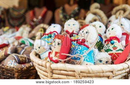 Colorful textile traditional female dolls as souvernirs sitting in basket, fair for tourists, on sale