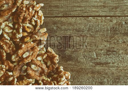 Baked walnuts for snack and bakery. Walnuts is good for health diet food raw material or ingredients for cooking and food.Vintage tone style of walnuts on rustic wood for background or wallpaper. Walnuts background concept with copy space.