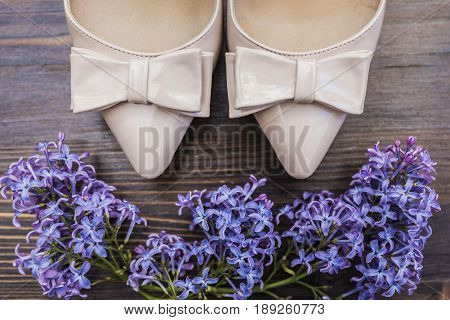 Beige lacquered shoes with a sharp nose and bow and bright lilac flowers on a dark wooden background