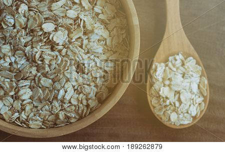 Oat flakes or oatmeal in wood bowl. Old-fashioned oat flakes put on rustic wood table. Rolled oat is clean food for health. Prepare oat flakes for bakery or cooking. Natural organic food in top view.