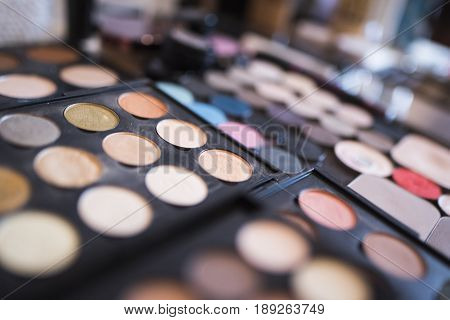 A pallet of powder of beige shades and eye shadows for shades of blue for professional make-up.