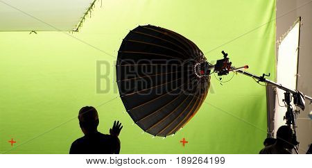 Big studio light equipments and man setting for shooting movie video or photo film and green screen background.