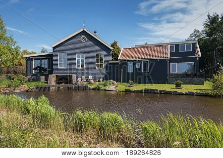 De Woude, Netherlands, April 30, 2017: Characteristic house iand also bucking n the village De Woude which is located on an island in the Alkmaarder and Uitgeester lake in The Netherlands
