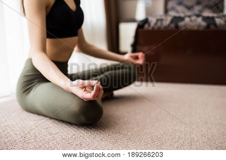 Yoga At Home. Attractive Young Woman Sitting On Lotus Position On Floor With Eyes Closed.