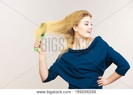 Woman brushing her long blonde hair using brush morning beauty routine. Haircare and hairstyling concept.