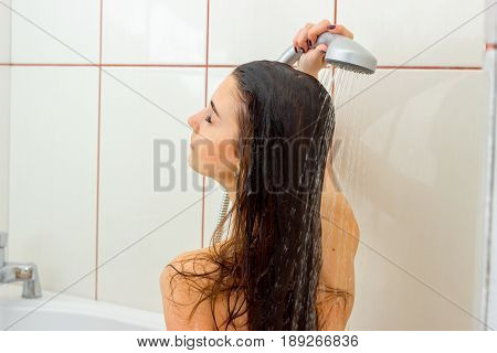 young girl with wet hair is standing under the shower closeup