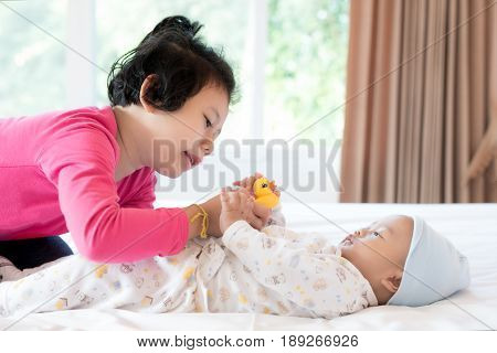 Asian baby brother and toddler sister playing fish doll in bedroom. Happy family.