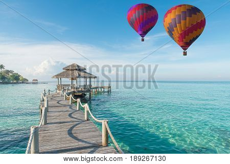 Colorful hot air balloon over Phuket beach with blue sky background Phuket Thailand Tropical hut and wooden bridge at holiday resort. Summer travel in Phuket Thailand.