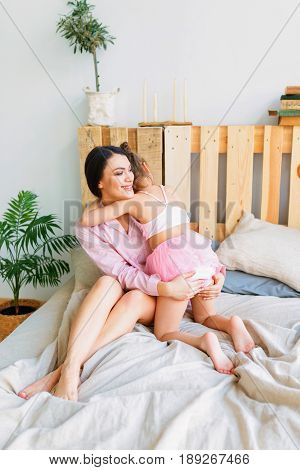 Happy loving family. Mother and daughter are doing hair and having fun. Mother and her child girl playing kissing and hugging.