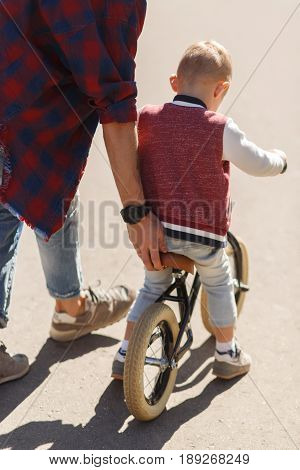 Dad teaches son to ride on bicycle in park during day