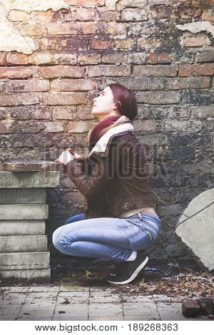 Young Woman With Leather Jacket Praying In Front Of An Old Wall