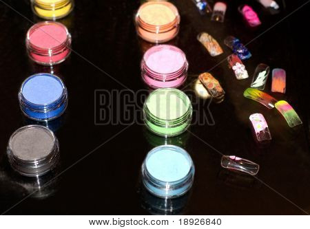 Set of powder cosmetic and fake nails on a mirror table (shallow dof)