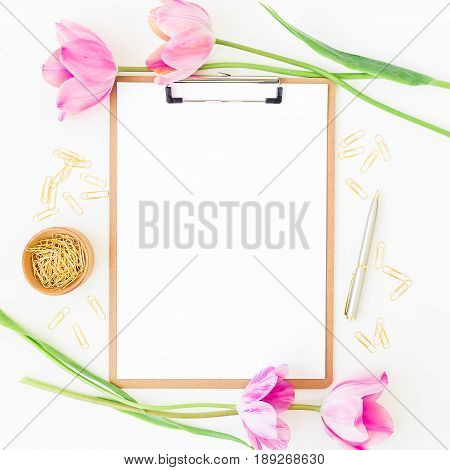 Freelancer or blogger workspace with clipboard, notebook, pink tulips and accessories on white desk. Flat lay, top view.