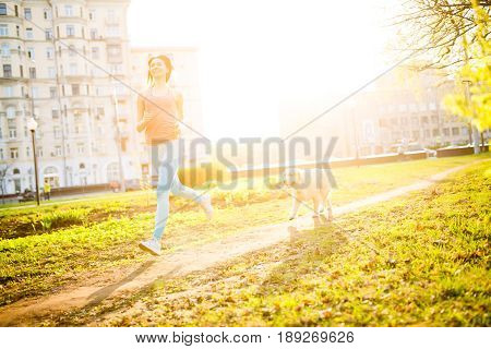 Sporty girl runing with dog on spring lawn,